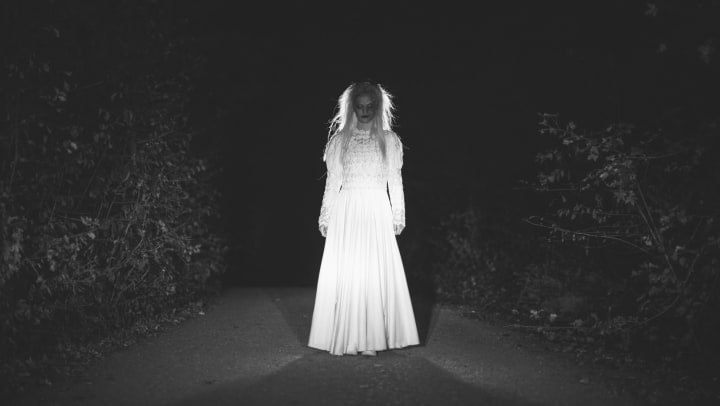Scary-looking woman in a Halloween costume standing in the road wearing a white dress.