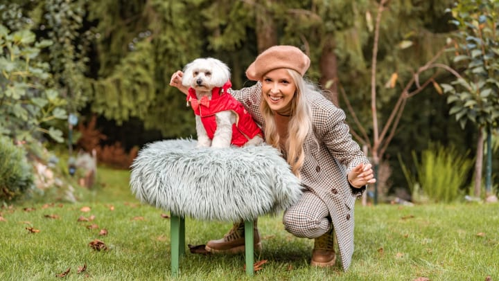 Woman standing behind a little dog in a puffy vest, posing for the camera.