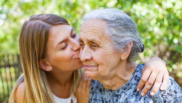 Young woman kissing senior woman on the cheek.