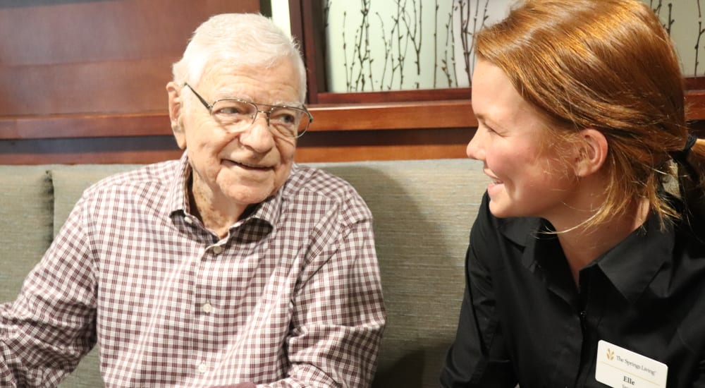 Resident chatting with caregiver at The Springs at Carman Oaks in Lake Oswego, Oregon.