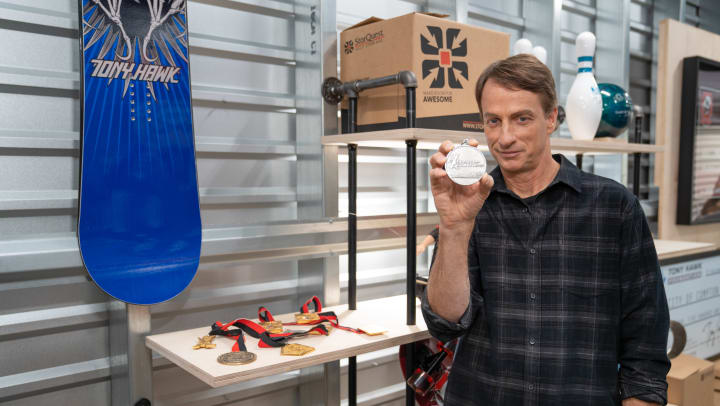 Tony Hawk holds up a medal while standing inside a storage unit