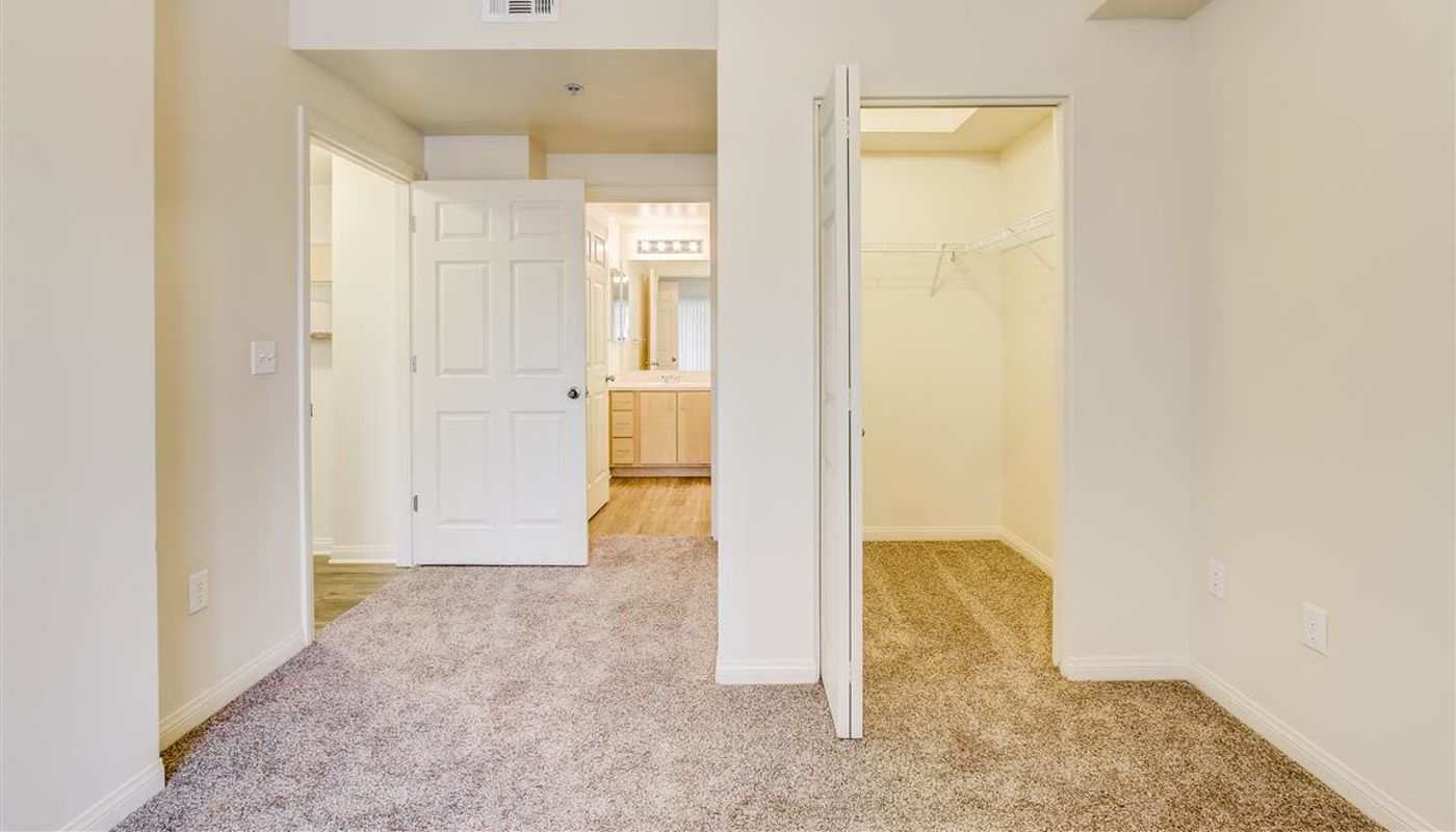 Bedroom with large walk-in closet, en suite bathroom, and plush carpeting in a model home at Sierra Oaks Apartments in Turlock, California