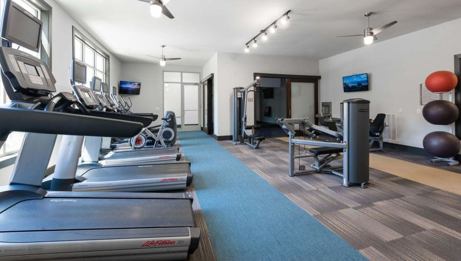 Fitness center with treadmills at Olympus at Waterside Estates in Richmond, Texas