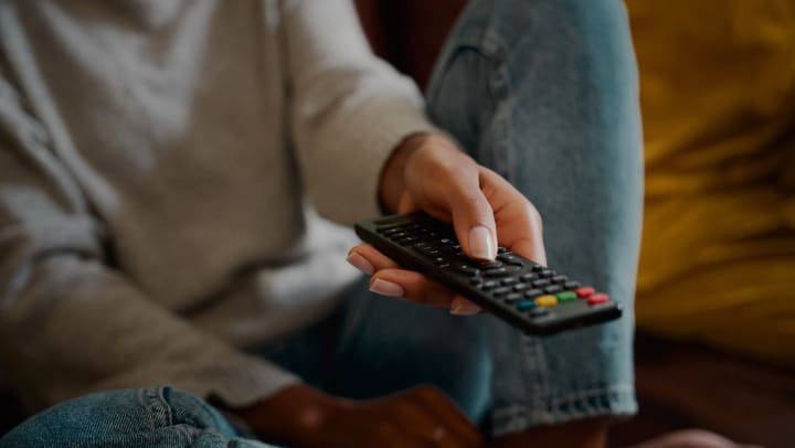Young person flipping through movies and shows on HBO max