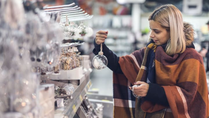 Woman wrapped in fall clothing in a store picking out ornaments