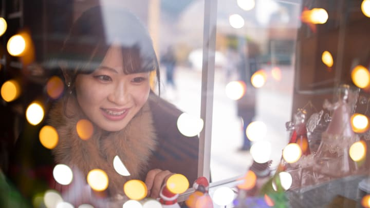 A woman looking into a window and smiling. Out of focus christmas lights all around her.