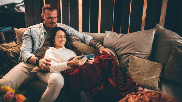 A smiling man and woman lounge on a sofa with velvet pillows and a plush blanket, as they look at her phone.