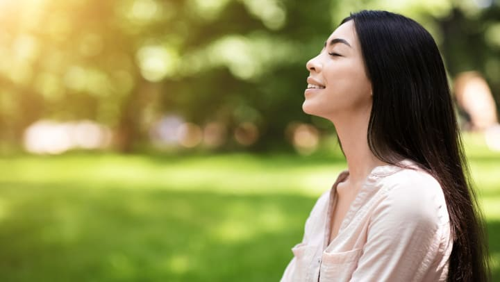 Profile view of smiling young woman with eyes closed in a green sunlit park