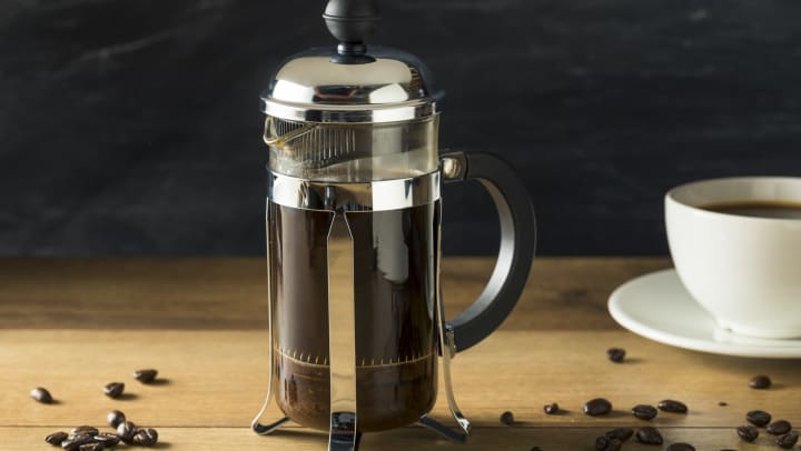 French press on a wood table with a mug and coffee beans.