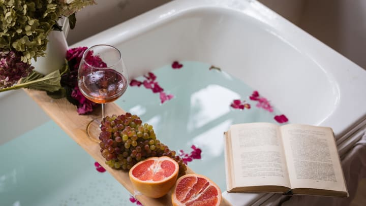 A white bathtub with flower petals floating in the water holds a tray with fruit, flowers, and a glass of wine, while an open book sits on the edge of the tub.