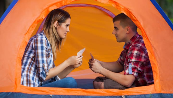 Man and woman in a tent with playing cards in their hands, looking in to each other's eyes.