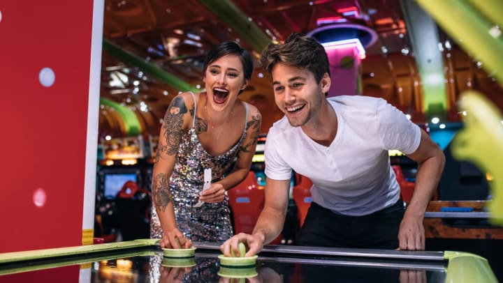 Young man and young woman playing air hockey in a colorful indoor arcade