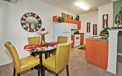 Dining area and modern kitchen with white appliances in model home at The Landing at Mansfield in Mansfield, Texas