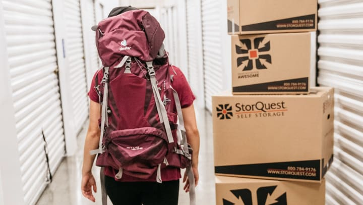 Woman wearing backpack beside a stack of moving boxes walks through a self storage corridor