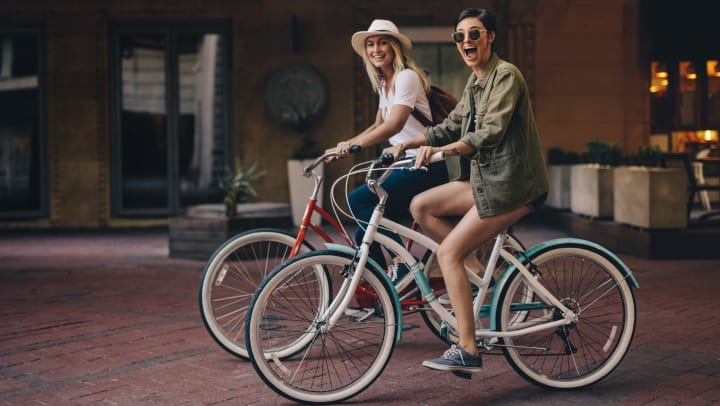 Female friends riding their bicycles on a city street.