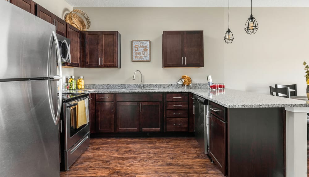 Spacious kitchen with granite countertops in a model home at Bonterra Apartments in Fort Wayne, Indiana
