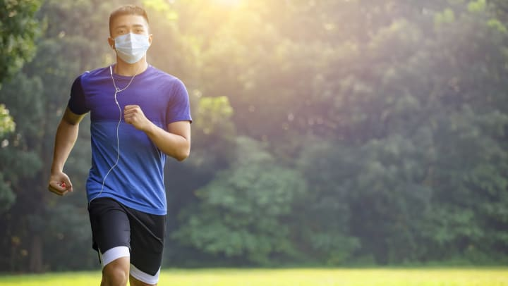 Man wearing mask and headphones, jogging.
