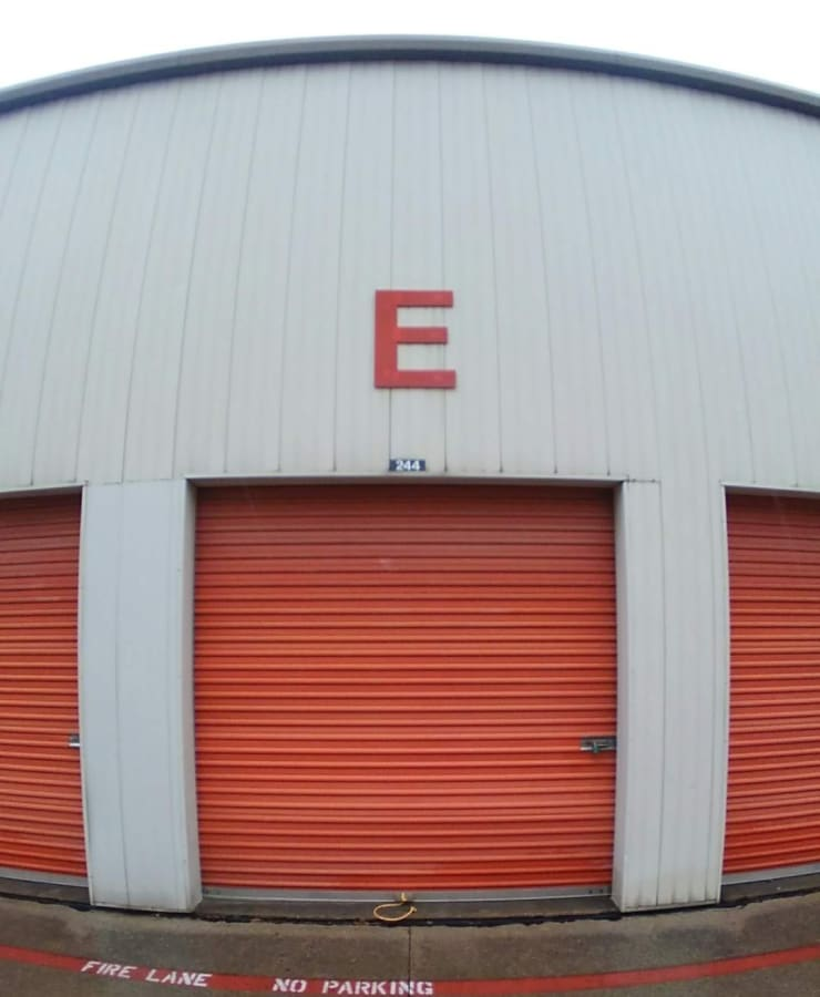 A row of outdoor units, with red doors closed, at StorageLand Rental Spaces in Arlington, Texas