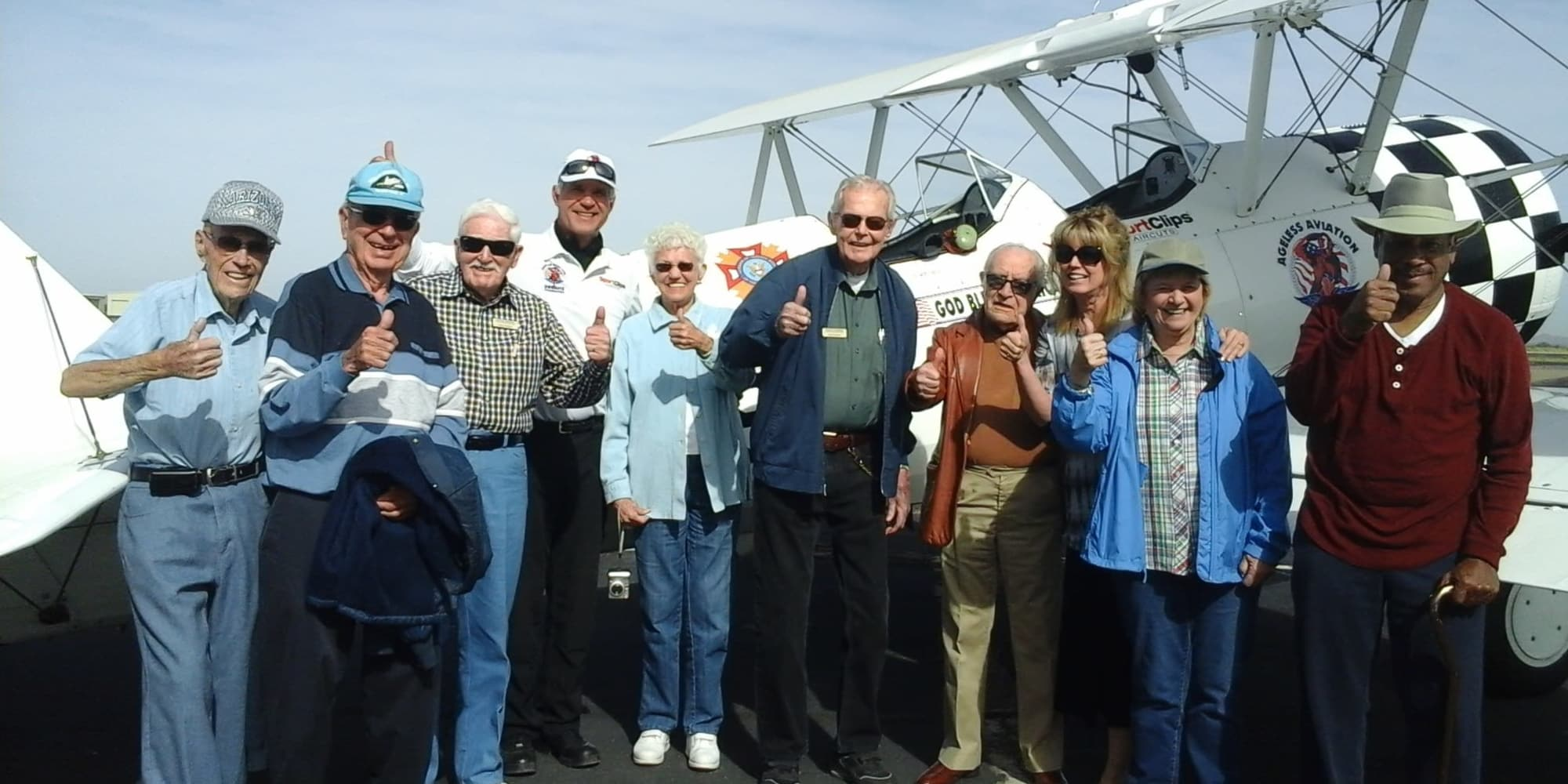 A group of residents from Desert Springs Gracious Retirement Living in Oro Valley, Arizona standing in front of a plane