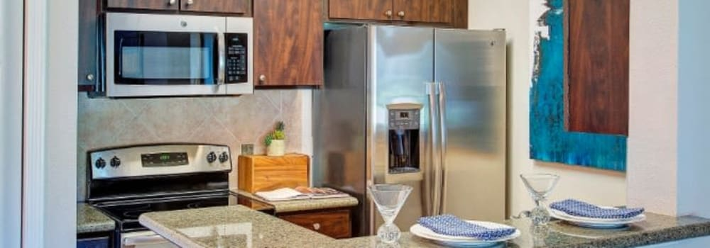 A kitchen with stainless-steel appliances at The Fuse at Park Row in Houston, Texas