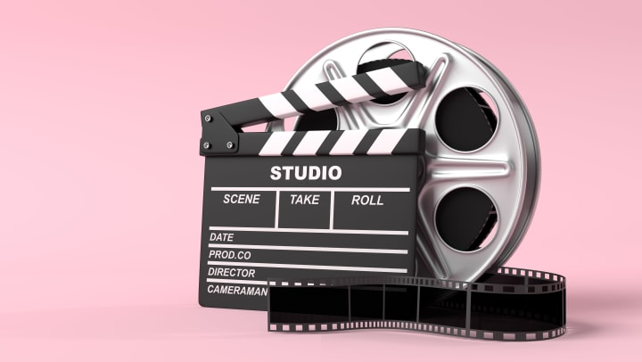Film reel with clapperboard isolated on bright pink background in pastel colors