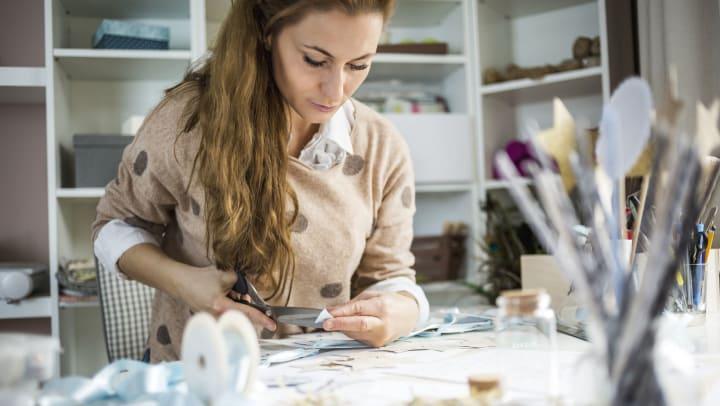 Woman cuts ribbon for DIY holiday crafts.