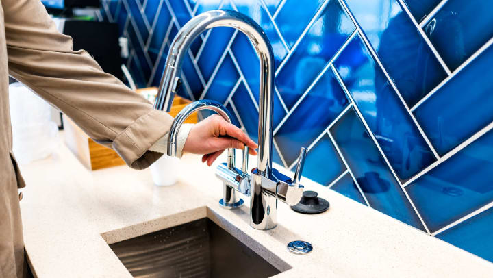 A kitchen sink with stainless steel faucet is surrounded by cream quartz countertops and a vibrant blue herringbone-patterned backsplash.
