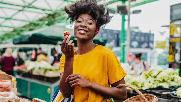 A smiling young woman at a farmers' market holds up a strawberry in one hand, and holds a shopping basket with some leafy greens in the other.