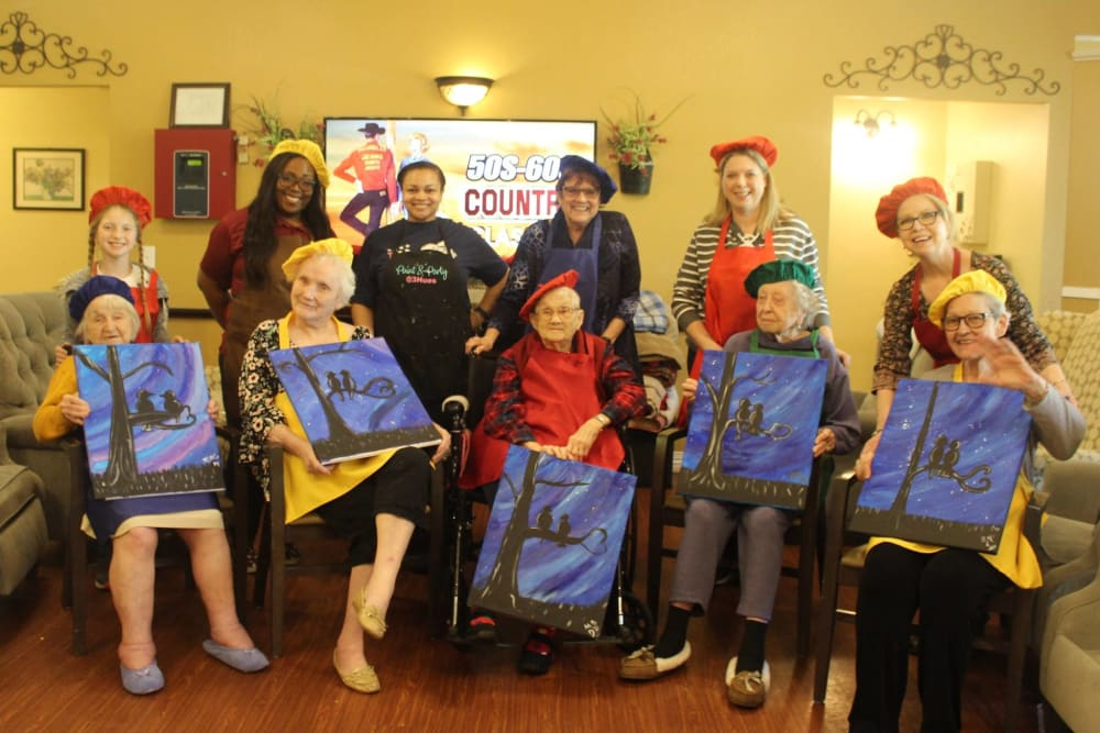 Residents holding their paintings up at Autumn Grove Cottage at Copperfield in Houston, Texas