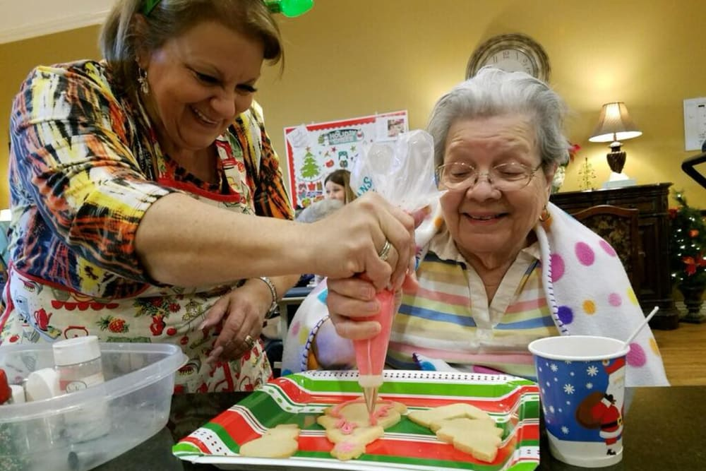 Residents decorating cookies together at Autumn Grove Cottage at The Heights in Houston, Texas