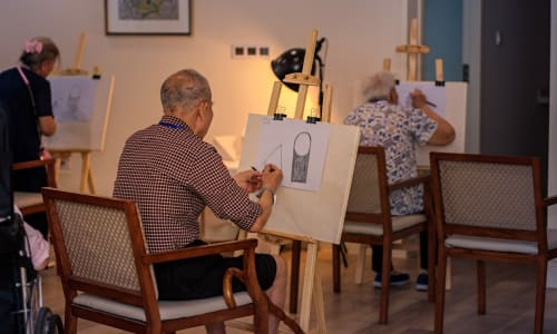 A resident working on a task at a Merrill Gardens china community