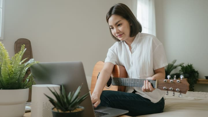 Resident learning to play guitar online in her new home at Olympus on Broadway in Carrollton, Texas