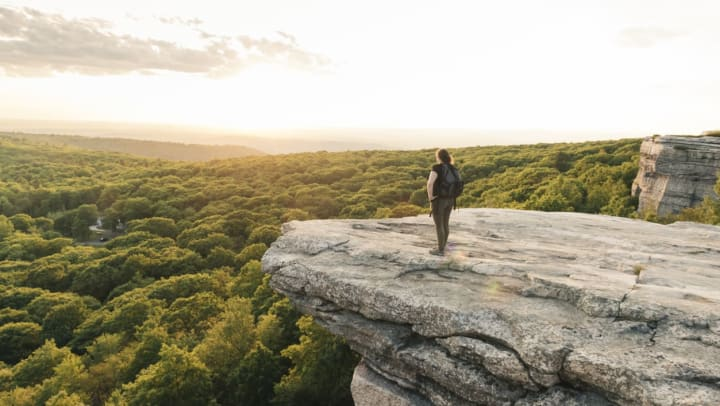 Woman stands on a rock ridge staring out onto forestland