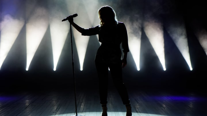 Woman's silhouetted on stage with microphone in hand and flood lights in background.