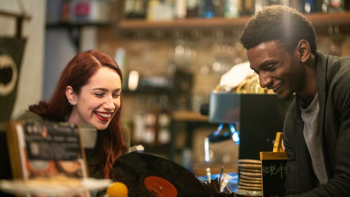 A smiling young man and woman look at vintage records in a music store