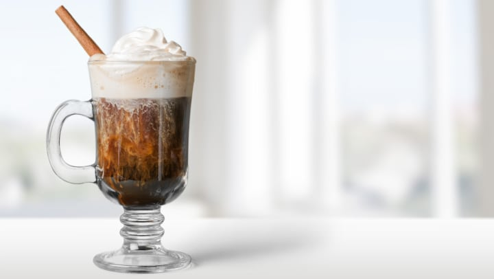 Coffee in a glass mug with whip cream and a cinnamon stick