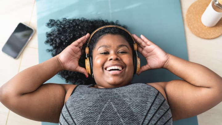 Smiling young woman lying on a yoga mat and exercising while wearing headphones