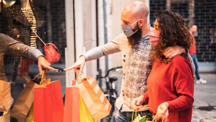 Man and woman holding shopping backs and looking through a display window at something man is pointing at