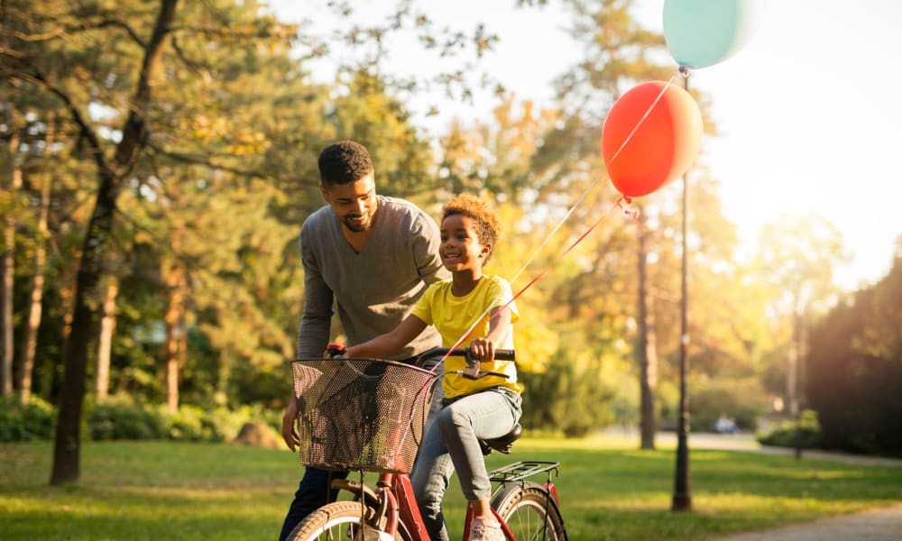 Resident teaching his son to ride a bike in our garden-style community at Oaks Lincoln Apartments & Townhomes in Edina, Minnesota