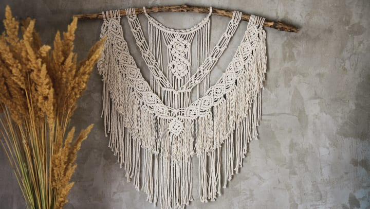 An elaborate macrame wall hanging is displayed on a concrete wall.