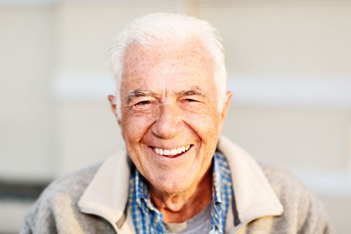 Resident smiling into the camera at Cedar Crest Memory Care in Lafayette, Louisiana