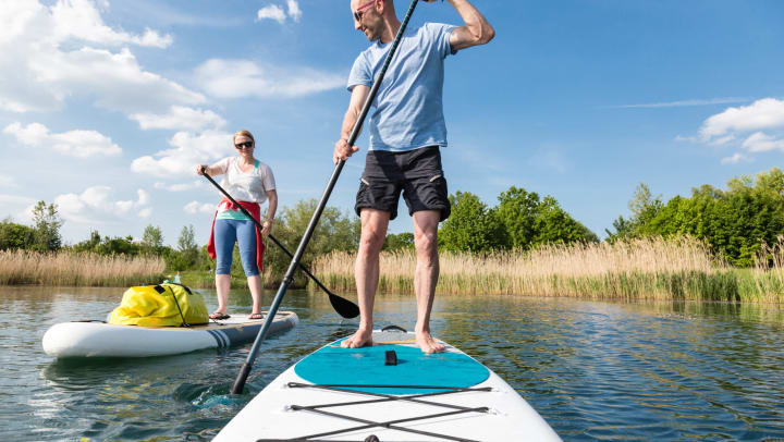 Couple paddle boarding in Irving, Texas near Olympus Las Colinas