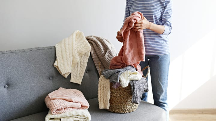 A woman folding up winter sweaters on her couch