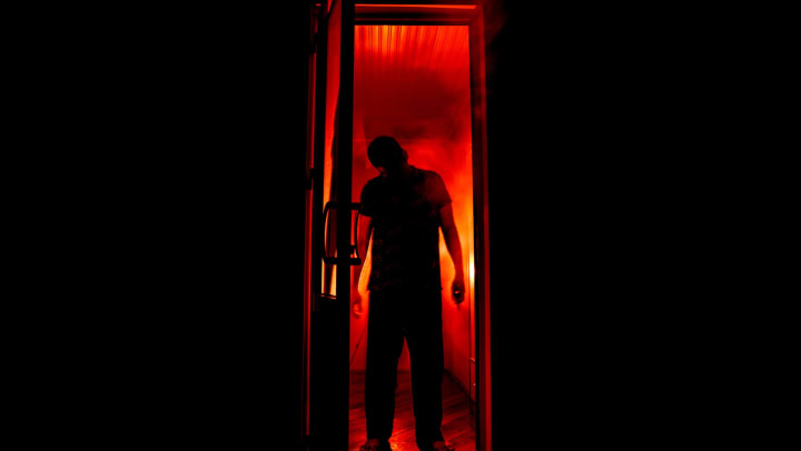 Tall scary figure standing in a doorway at a haunted house near The Davis