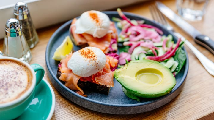 Poached eggs with salmon and half an avocado drizzled with olive oil on a plate