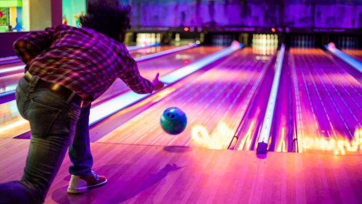 Man tossing a bowling ball down a lane toward a set of pins.