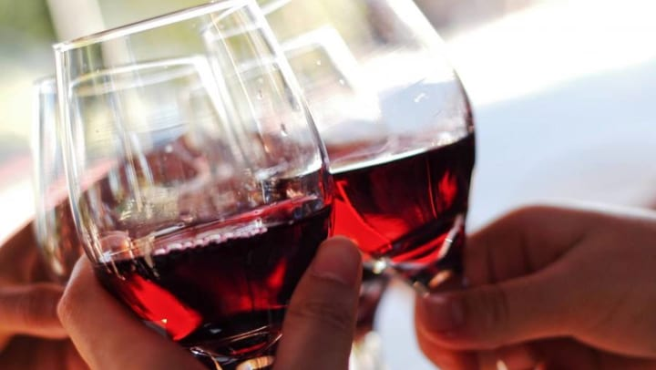 Close-up of three hands holding glasses of red wine while making a toast.