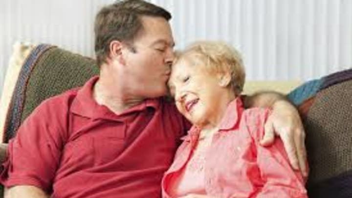 A man kissing his elderly mother on the forehead.