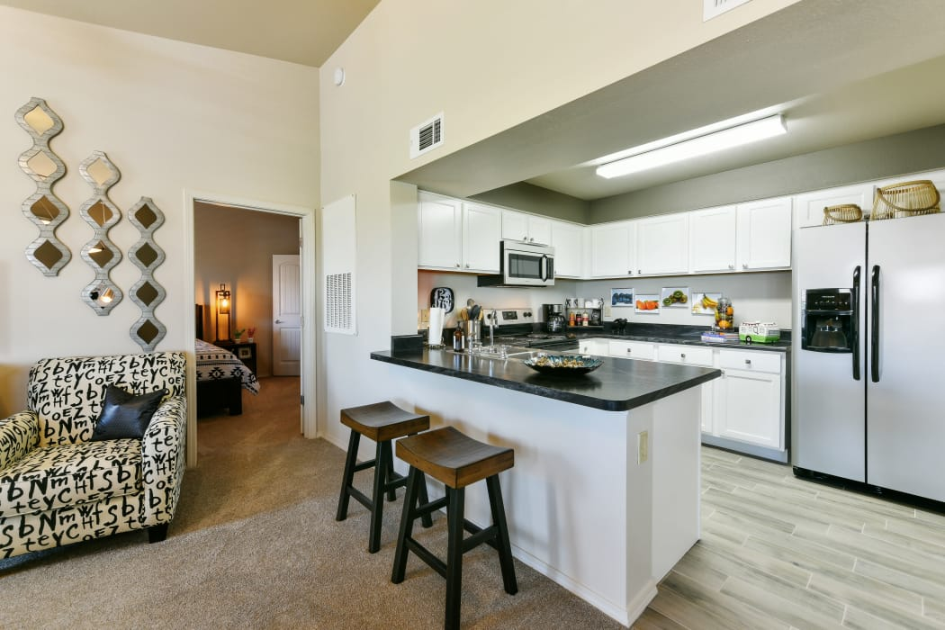 Kitchen with bar-style seating at Cottages at Abbey Glen Apartments in Lubbock, Texas