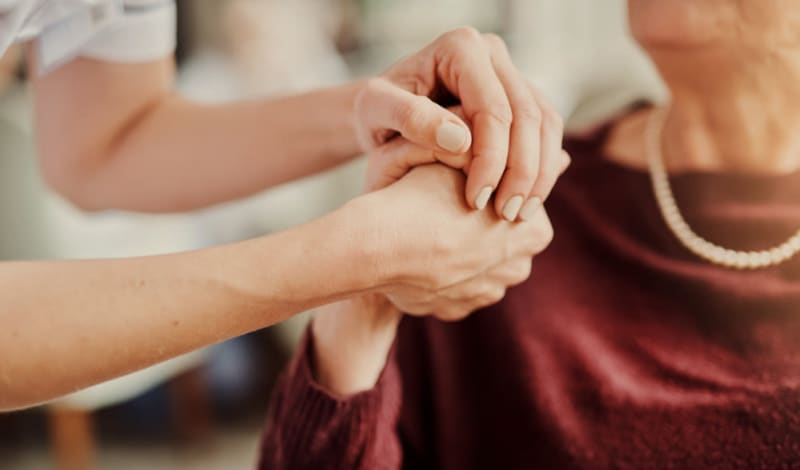 Family members holding hands at Hayden Grove Senior Living in Bloomington, Minnesota